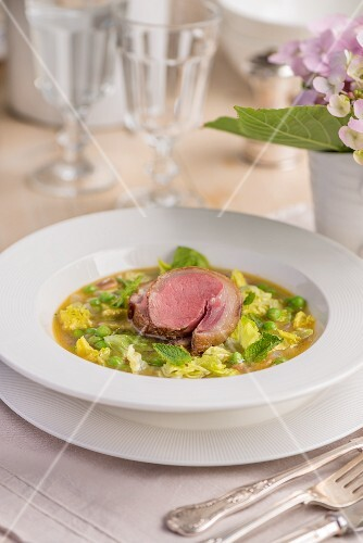 Pea soup with duck breast on a garden table