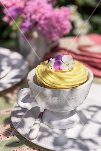 A cupcake decorated with vanilla cream and pansies on garden table