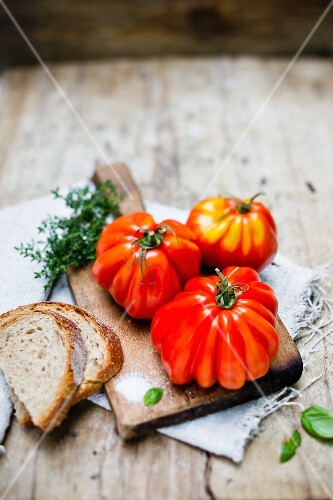 Three beefsteak tomatoes on a chopping board with salt and bread