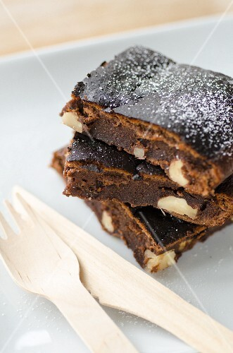 Three brownies with nuts next to wooden cutlery