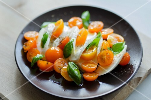 A salad of orange cocktail tomatoes, mozzarella and basil