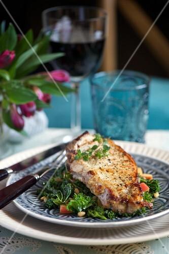 A pork chop with kale