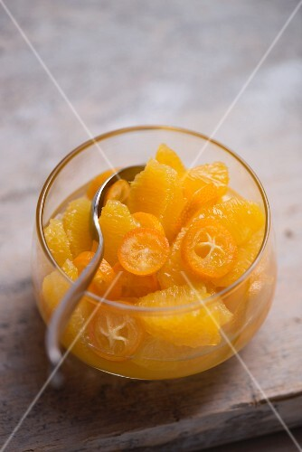 Fruit salad made of fresh oranges and kumquats in a glass bowl