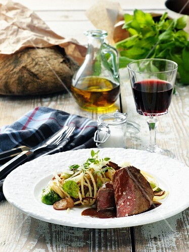 Beef fillet with pasta and a glass of red wine