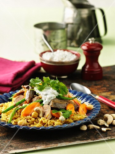 Lamb and chicken with yoghurt sauce, carrots and cashew nuts on a bed of rice
