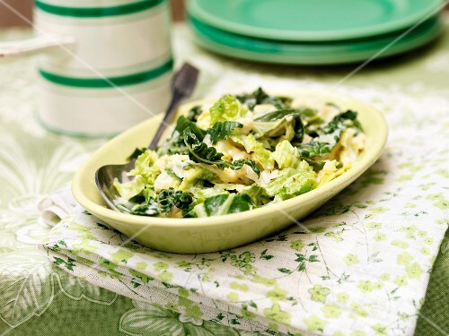 A cabbage medley with cream on a lime-green serving platter
