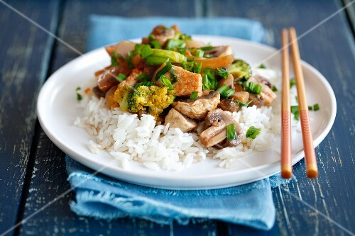 Fried pork loin with mushrooms and broccoli on a bed of rice (Asia)