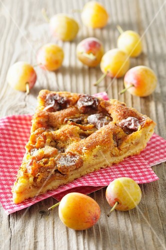 A slice of yellow plum tart on a checked napkin