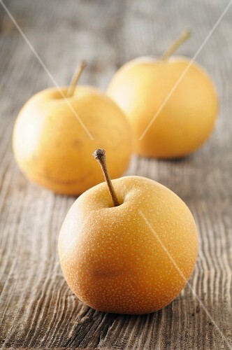 Three Nashi pears on a wooden surface