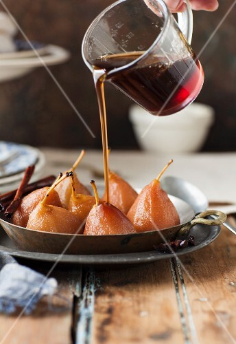Poached pears being made: syrup being poured over pears