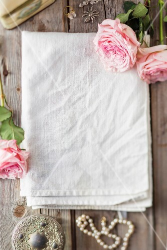 Linen cloth decorated with flowers on wooden surface