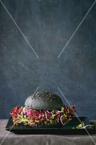 A homemade veggie burger with beetroot, sprouts, mushrooms and lettuce