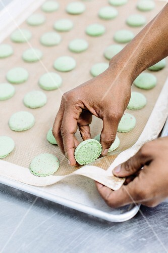 Green macaroons being removed from a baking tray