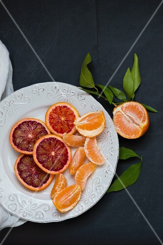 Slices of blood oranges and mandarin segments on a white plate