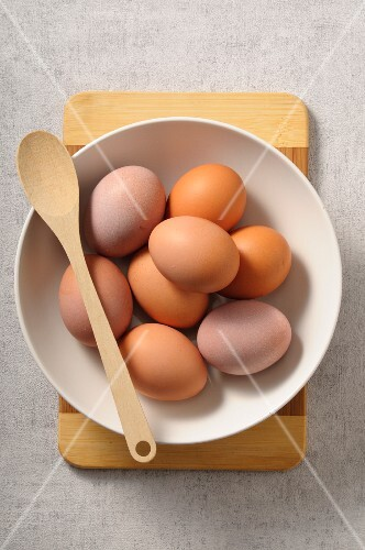 A bowl of fresh eggs with a wooden spoon