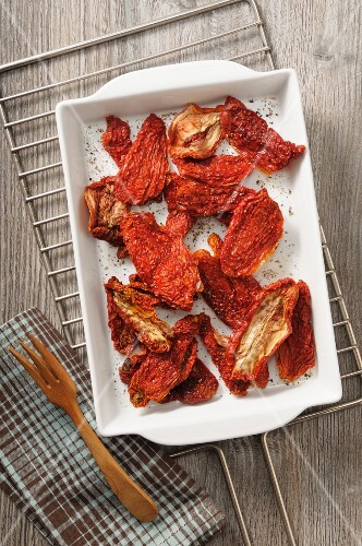 Dried tomatoes with salt and ground black pepper (seen from above)