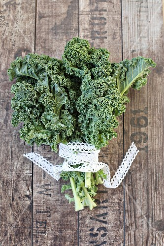 Kale tied with a lace ribbon on a wooden surface