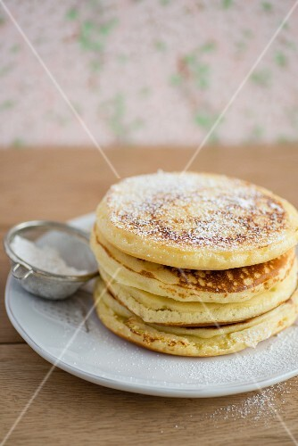 A stack of pancakes with icing sugar