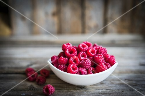A bowl of fresh raspberries on a rustic wooden surface