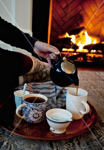 A woman sitting by a fireplace pouring tea into a cup