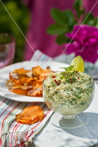 Mackerel and avocado cream with root vegetable crisps on a table outside