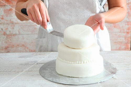 A multi-tier cake being decorated with white fondant icing