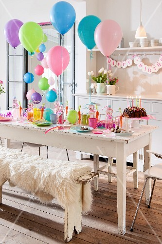Festively set table and colourful balloons for child's birthday party