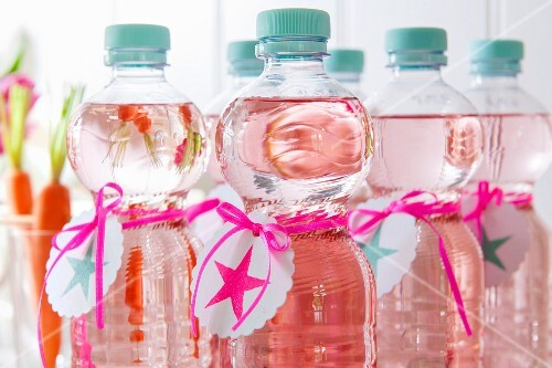 Bottles of water with self-printed labels and ribbons