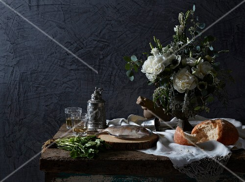 An arrangement featuring a bunch of flowers, bread, fish and a tin jug