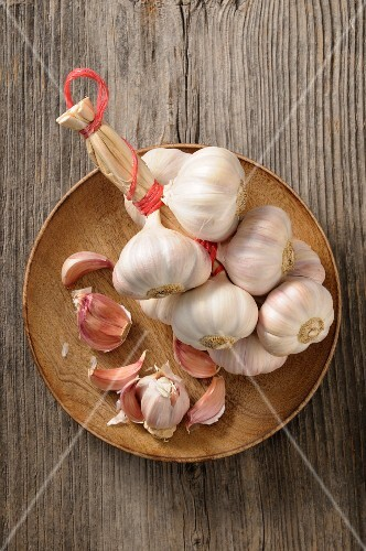A string of garlic and cloves of garlic on a wooden plate