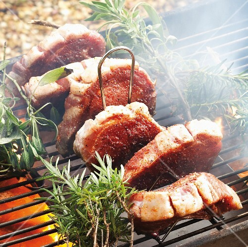 Pork chops with rosemary and sage on a barbecue