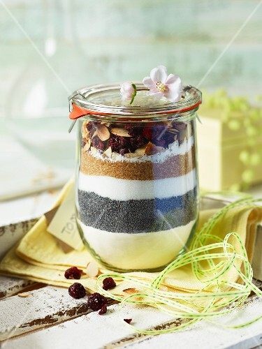 A baking mixture for poppyseed cake with cherries in a glass as a gift