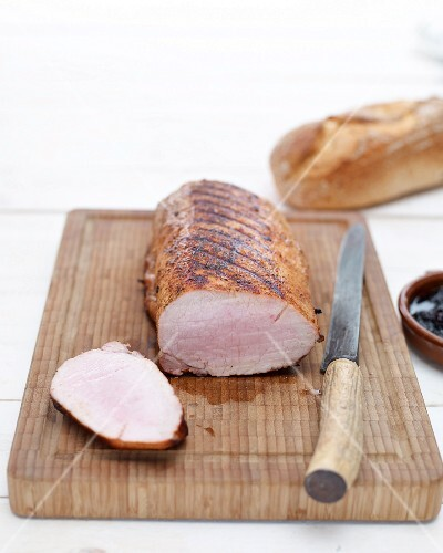 Grilled pork loin, sliced, on chopping board