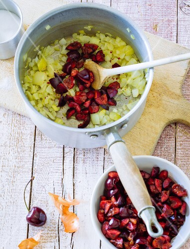 Ingredients for onion and cherry chutney being sautéed in a saucepan