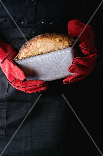 A baker wearing red oven gloves holding a tin of freshly baked bread