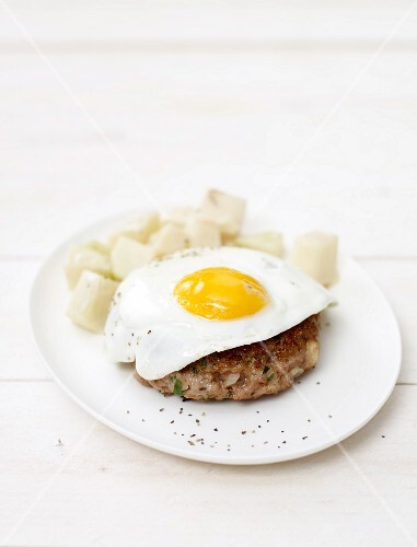 A burger topped with a fried egg served with kohlrabi