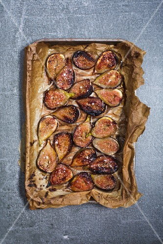 Baked figs with salted honey on a baking tray (seen from above)