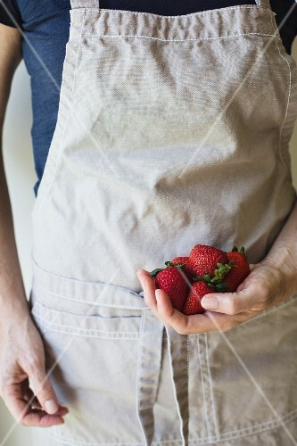 A person holding fresh strawberries