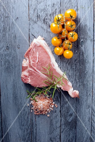 A fresh veal chop, salt, rosemary and yellow tomatoes on wooden surface