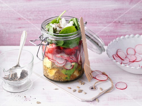 Layered quinoa and spinach salad with goat's cheese in a jar