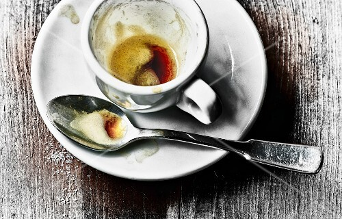 The remains of coffee in an espresso cup and on a spoon on a saucer