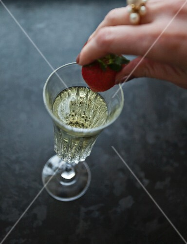 A woman placing a strawberry in a glass of prosecco
