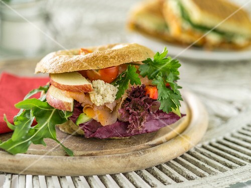 A bagel with salmon, cream cheese, lettuce, apples and tomatoes