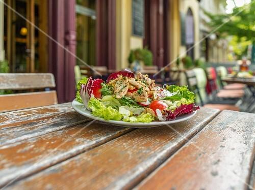 Gemischter Blattsalat mit Tomaten und Radieschen auf Holztisch vor Restaurant