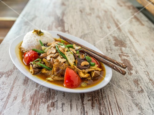 Chicken with mushrooms, cashew nuts, tomatoes, beans and rice (Asia)