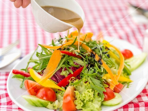 Dressing being poured over a mixed leaf salad with rocket, peppers and tomatoes