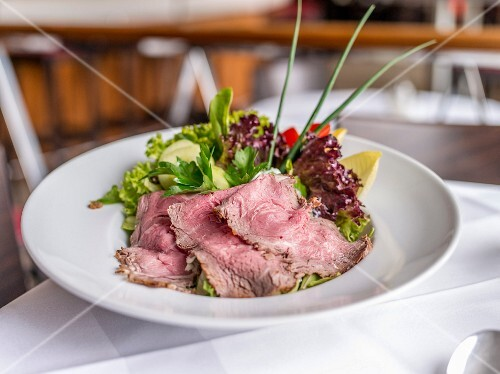 Roast beef with a mixed leaf salad in a restaurant