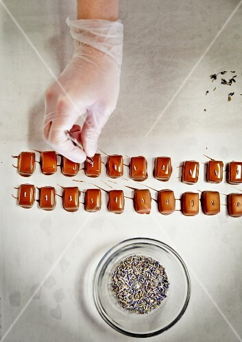 Homemade chocolate pralines being garnished with lavender flowers