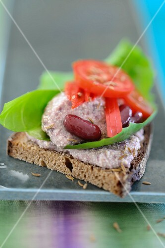 Slice of bread topped with a tofu and bean spread and tomatoes