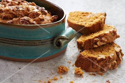 Bread topped with nuts in a decorative baking dish